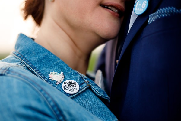 Badges on collar of bride's denim jacket