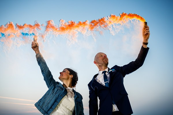 Bride and groom waving orange smoke bombs