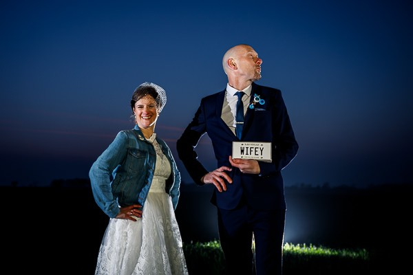 Groom doing funny pose holding wifey sign