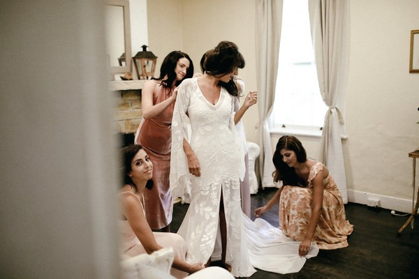 Bridesmaids helping bride get dressed