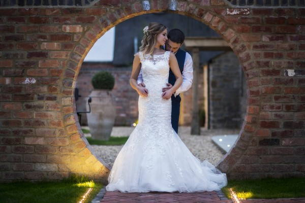 Bride and Groom in Front of Circle Hole in Wall at Blackwell Grange