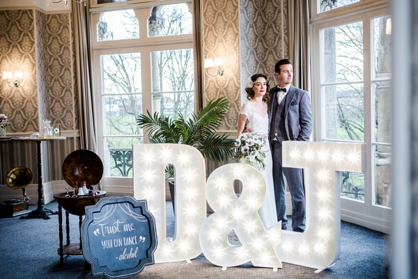 1920s bride and groom behind light up letters at The Duke of Cornwall Hotel