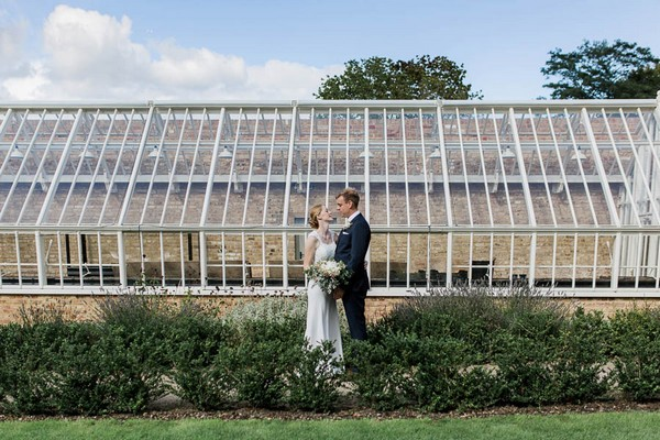 Bride and groom in front of greenhouse at Langtons House
