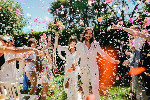 Bride and groom walking through a colourful shower of confetti