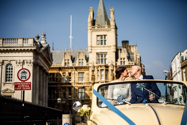 Bride and groom kissing in VW Beetle in Cambridge city centre