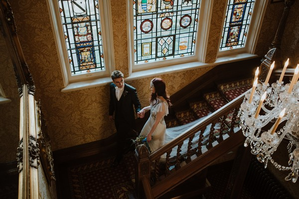 Bride and groom walking down stairs at Kilworth House