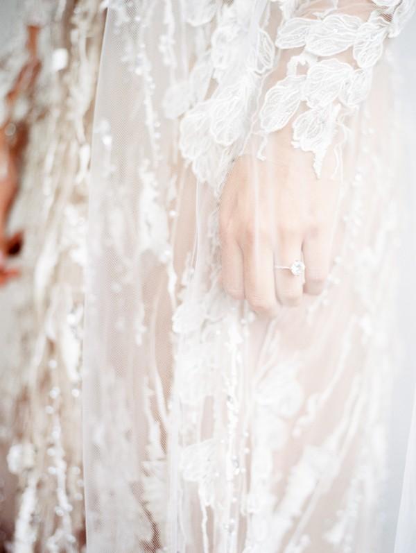 Ring on bride's finger under veil