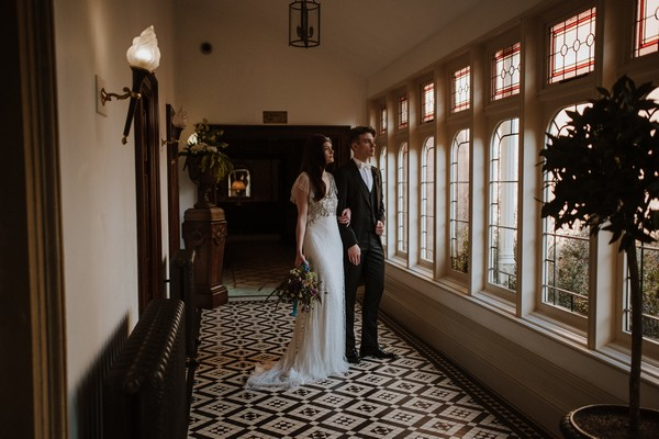 Bride and groom looking out of window at Kilworth House