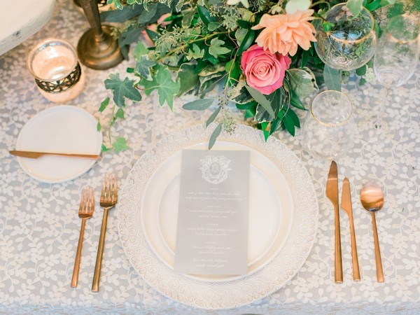 Grey wedding menu on plate with gold cutlery