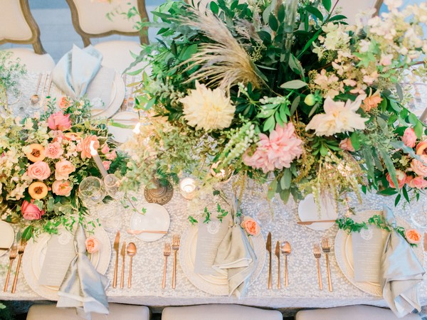 Wedding table styled with flowers, foliage and gold