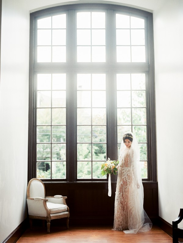 Bride standing by large windows