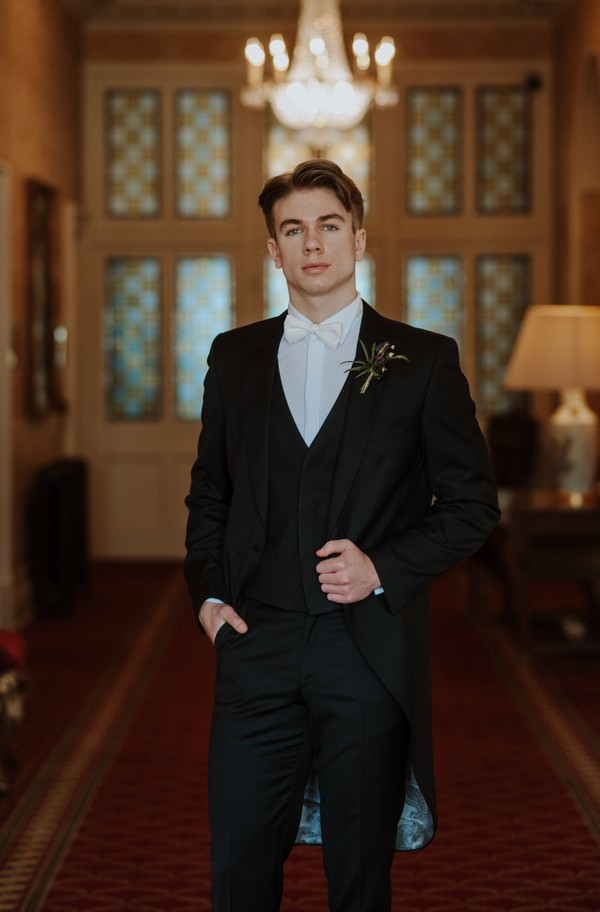 Groom wearing smart suit and white tow tie