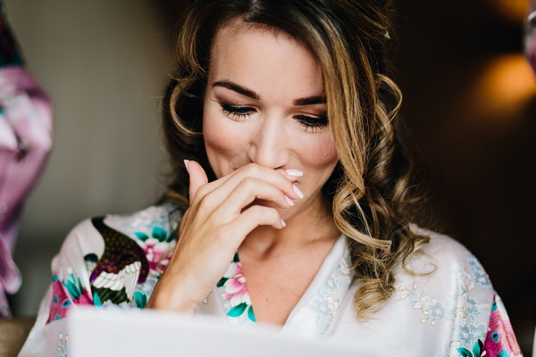 Emotional bride looking at gift from groom