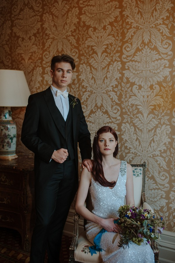 Groom standing next to bride sitting in chair