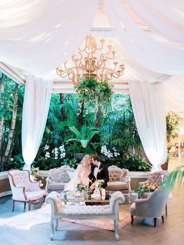 Bride and groom sitting n couch below chandelier