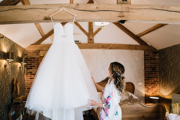 Bride looking at wedding dress hanging from beam