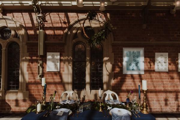 Foliage wreath hanging above wedding table