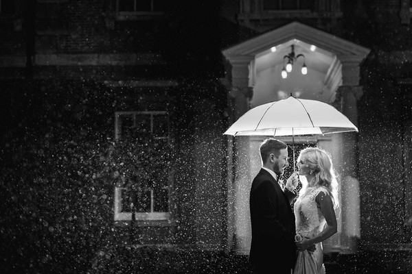 Black and white picture of bride and groom under umbrella in the rain - Picture by Photography by Suzanne Fossey