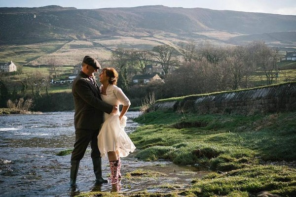 Bride and groom in wellies standing in stream in countryside - Picture by Emma and Rich