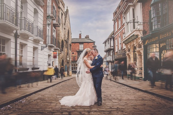 Bride and groom on cobbled street in Lincoln with blurred people walking past - Picture by AWPhotographic
