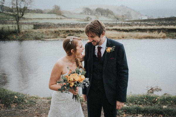 Bride and groom laughing by lake - Picture by Louise Jacob Photography