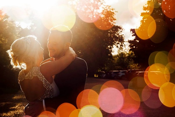 Bride and groom hugging with light spots reflecting off camera lens - Picture by Purple Pear Tree Photography