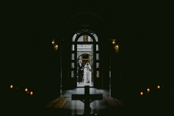 Bride and groom entering darkly lit chapel - Picture by Rares Ion