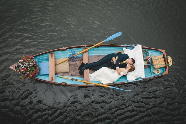 Bride and groom laying down in rowing boat - Picture by Mark Leonard Photography