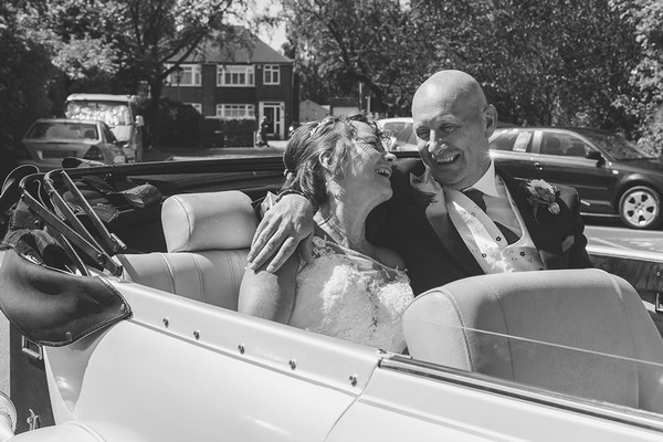 Happy bride and groom sitting in back of convertible wedding car - Picture by Life Through A Lens - Rachel Ellis Photography