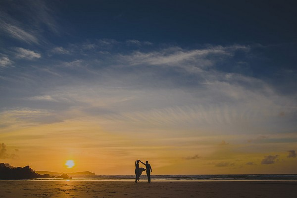 Silhouette of bride and groom dancing on beach at sunset - Picture by Abi Riley Photography