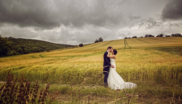Bride and groom kissing in a field - Picture by Bev Downie Photography