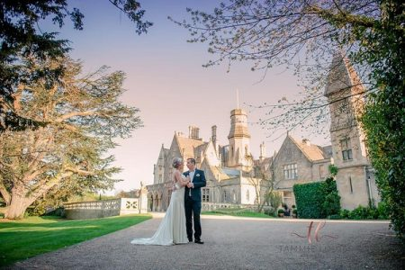 Bride and groom standing in front of Manor by the Lake - Picture by Tammie Louise Photography