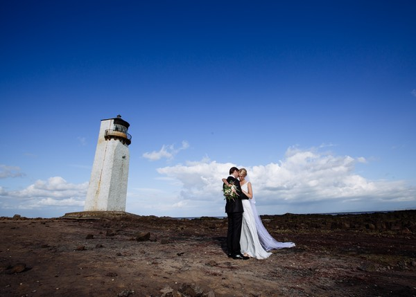 Bride and groom on Southerness beach with lighthouse in background - Picture by Giles Atkinson Photography