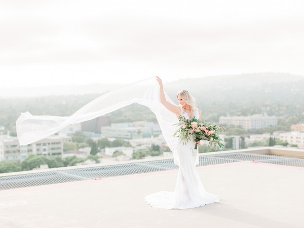 Bride with long cape blowing in wind