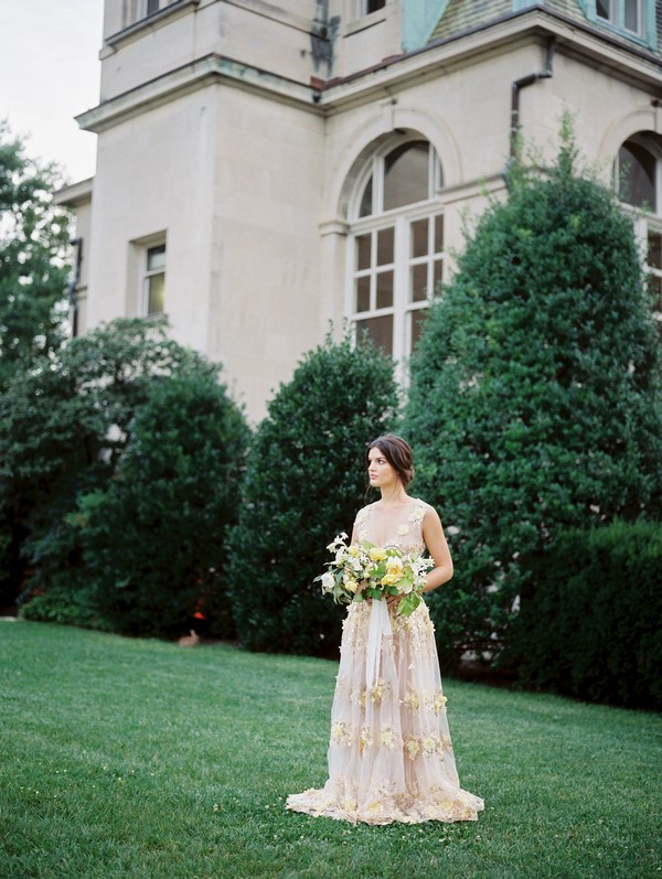 Bride holding bouquet on lawn