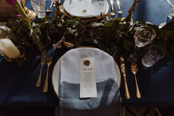 Wedding place setting with dark blue and gold styling