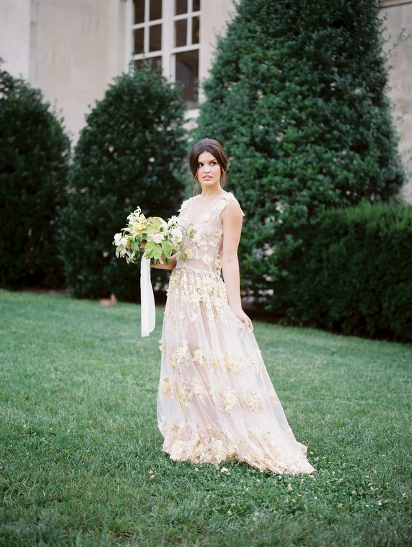 Bride on lawn holding bouquet