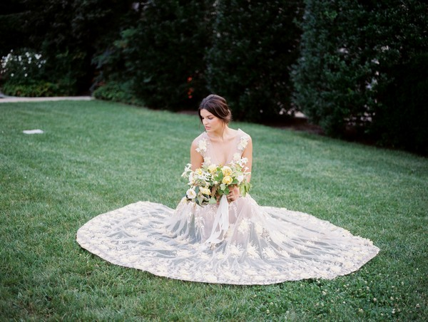 Bride sat on lawn with dress pulled out around her