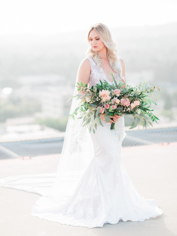 Bride holding bridal bouquet of foliage and peach flowers