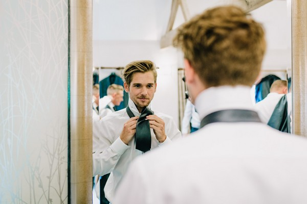 Groom doing tie in mirror