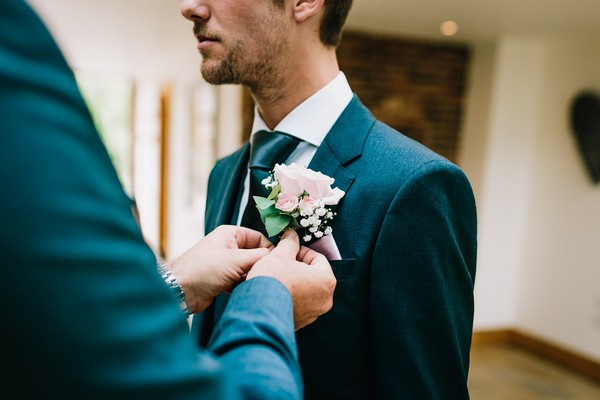 Groomsman helping groom with buttonhole