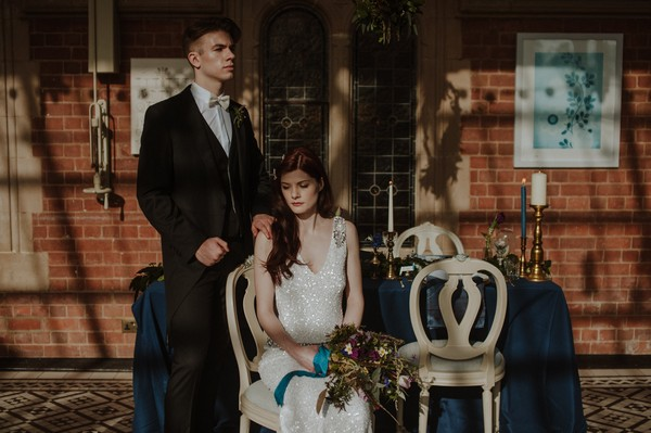 Groom standing next to bride sitting in front of wedding table
