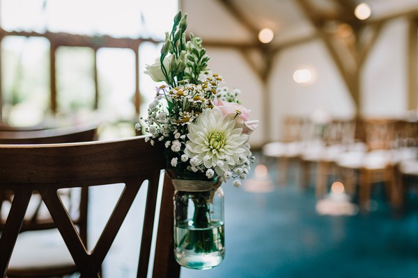 Jam jar of flowers tied to wedding ceremony chair