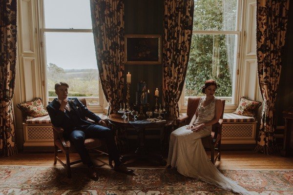 Bride and groom sitting next to cake table at Kilworth House