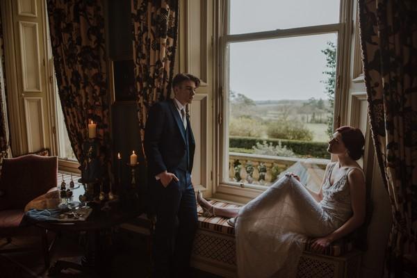 Groom standing by bride sitting on window ledge