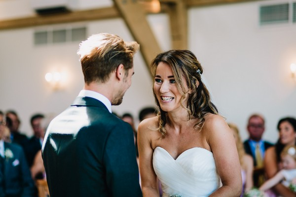 Bride and groom facing each other during wedding ceremony at Mythe Barn