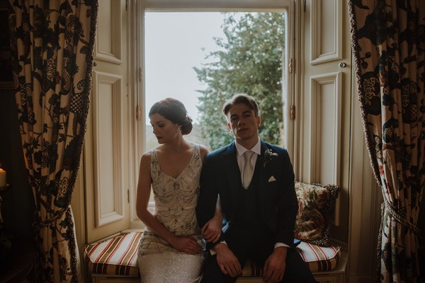 Bride and groom sitting in front of window at Kilworth House