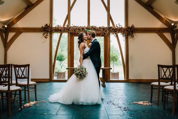 Bride and groom kissing in ceremony room at Mythe Barn