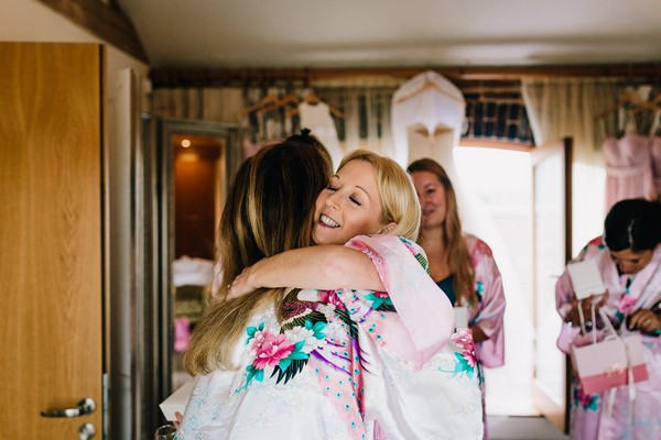Bridesmaid hugging bride
