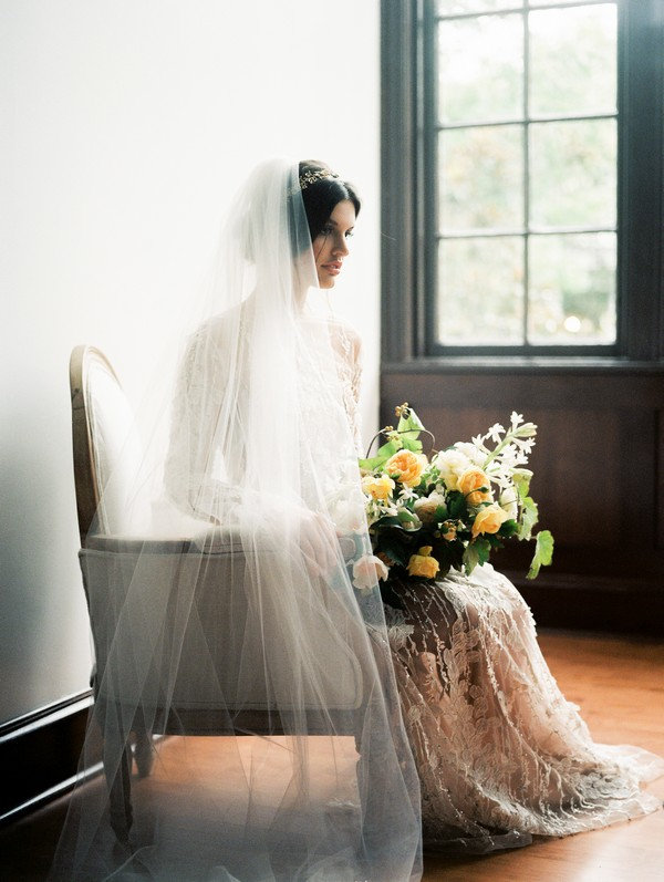 Bride sitting in chair holding bridal bouquet with yellow flowers